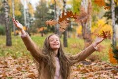 Une fille d'adolescent dans un manteau rit et jette des feuilles en automne photographie stock
