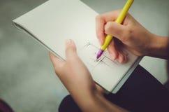 Une fille d'adolescent dessine un stylo dans un carnet images libres de droits