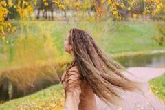 Une fille d'adolescent tourne sous le feuillage d'un bouleau dans l'autu photographie stock libre de droits