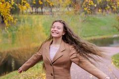 Une fille d'adolescent tourne sous le feuillage d'un bouleau dans l'autu photo libre de droits