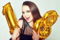 Une fille d'anniversaire sur son 18ème anniversaire avec des baloons de nombre d'or La fille dix-huit excitée avec le vert compos image stock