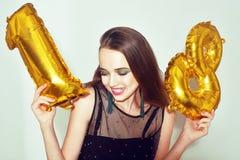 Une fille d'anniversaire sur son 18ème anniversaire avec des baloons de nombre d'or La fille dix-huit excitée avec le vert compos photo libre de droits