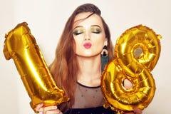 Une fille d'anniversaire sur son 18ème anniversaire avec des baloons de nombre d'or La fille dix-huit excitée avec le vert compos photos libres de droits