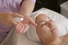 Une fille d'aspect asiatique dans un salon de beauté Un esthéticien professionnel serre un produit cosmétique de bouteille blanch image stock