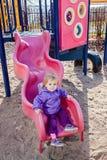 Une fille d'enfant en bas âge d'an jouant sur le terrain de jeu d'enfants Photographie stock libre de droits