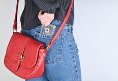 Une fille dans des pantomimes a adapté des jeans, un chandail et avec un sac rouge sur le bord retire une rétro cassette sonore d photographie stock