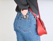 Une fille dans des pantomimes a adapté des jeans, un chandail et avec un sac rouge sur le bord retire une rétro cassette sonore d images stock