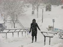 Une fille dans l'?quipement noir dans la temp?te de chute de neige importante ? UWM Photos libres de droits