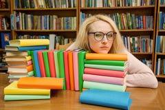 Une fille dans la bibliothèque regarde mystérieusement par des verres images stock
