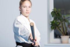 Une fille dans le hakama noir se tenant dans la pose de combat avec le bâton en bois de jo Foyer sélectif Image stock