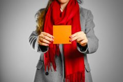 Une fille dans le manteau gris et l'écharpe rouge tient un squ vide propre orange photographie stock libre de droits