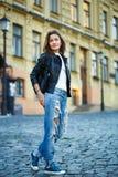 Une fille dans les espadrilles, les jeans et une veste en cuir se tient sur une ville Photographie stock libre de droits
