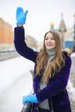 Une fille dans les gants bleus quelqu'un salue Photo stock