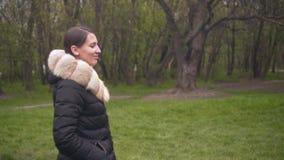 Une fille dans les promenades noires chaudes d'une veste La fille et la caméra se déplacent en parallèle Les sourires et les rire banque de vidéos
