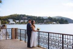 Une fille dans une robe de mariage avec un bouquet des supports de fleurs sur le dock avec un bouquet des fleurs dans sa main et  Image stock