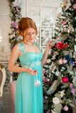 Une fille dans une robe de soirée à côté d'un arbre de Noël ` S Ève de nouvelle année Noël Image stock