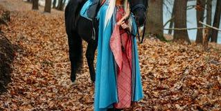 Une fille dans une robe rose de vintage, avec de longs cheveux, une blonde dans un cap bleu et démodé, supports près d'un cheval, image libre de droits
