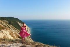 Une fille dans une robe rose saute sur le bord de la mer et sourit Images stock
