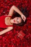 Une fille dans une robe rouge, mensonges dans les pétales de rose près d'un boîte-cadeau et tient sa main près de la tête image stock
