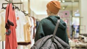 Une fille dans un chandail vert et un chapeau jaune marche par un stock de choses et choisit quoi acheter Choses de contacts dess clips vidéos