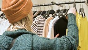 Une fille dans un chandail vert et un chapeau jaune marche par un stock de choses et choisit quoi acheter Choses de contacts dess banque de vidéos