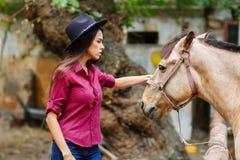 Une fille dans un chapeau et une chemise se tient vis-à-vis du cheval et de la repasser outside photos stock