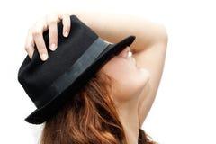 Une fille dans un chapeau noir Photographie stock libre de droits
