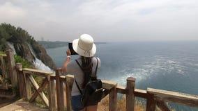 Une fille dans un chapeau se tient près d'une barrière en bois et prend la vidéo d'une belle cascade banque de vidéos