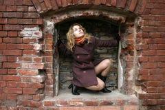 Une fille dans un encastrement de brique Photographie stock