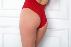 Une fille dans un maillot de bain rouge se tient en longueur se penchante contre a Images libres de droits