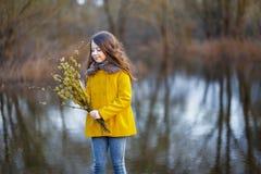 Une fille dans un manteau jaune dans la forêt en premier ressort avec une branche de saule des brindilles Un freshet ou des haute image stock