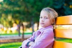 Une fille dans un manteau rose a plié ses bras dans l'avant et regarder l'appareil-photo, se reposant sur un banc jaune en parc photo libre de droits