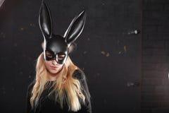 Une fille dans un masque noir photo stock
