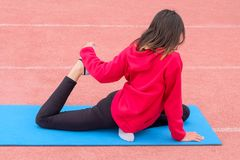 Une fille dans un T-shirt rouge et un pantalon noir exécute des exercices de forme physique sur un tapis bleu de gymnase en plein Photo libre de droits