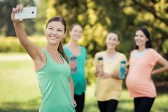 Une fille dans un T-shirt vert fait un selfie avec ses trois amies enceintes Photographie stock libre de droits