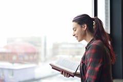 Une fille dans une chemise lisant un livre Photographie stock