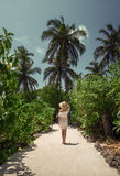 Une fille dans une robe blanche sous les palmiers maldives Vacances récréation tropiques Image stock