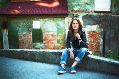 Une fille dans une veste en cuir, des jeans et des espadrilles ; Se reposer près d'un r Images libres de droits