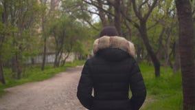 Une fille dans une veste noire chaude marche par les bois La fille entre dans l'avant, la caméra la suit clips vidéos