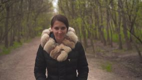 Une fille dans une veste noire chaude marche par les bois La fille entre dans l'avant, la cam?ra la suit clips vidéos
