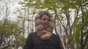 Une fille dans une veste noire chaude marche par les bois La fille suit la cam?ra tire de haut en bas banque de vidéos