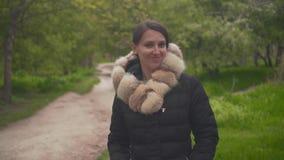 Une fille dans une veste noire marche par les bois Les clins d'oeil de fille à ses sourcils et sourires provocantement dans le ca banque de vidéos