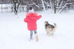 Une fille dans une veste rose et les courses de chapeau dans la neige avec un chien de traîneau font Photos stock
