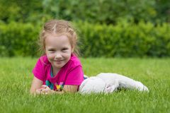 Une fille de 4 années jouant avec un jouet câlin sur l'herbe en parc Photographie stock libre de droits