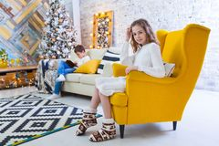 Une fille de 10 ans s'assied sur une chaise jaune dans la maison avant les vacances de Noël À l'arrière-plan un garçon s'assied Photographie stock libre de droits