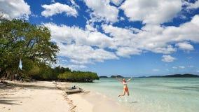 Une fille de bikini sautant sur la plage blanche Photo libre de droits