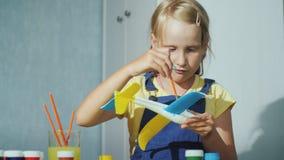 Une fille de blonde peint un avion modèle Activités éducatives pour des enfants clips vidéos