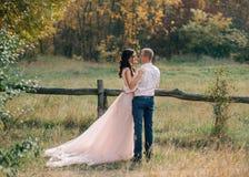 Une fille de brune dans une robe rose luxueuse étreint un homme élégant dans une chemise rose et des pantalons bleus Un couple af photographie stock libre de droits