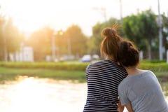 Une fille de couples a l'amour et regarder ainsi que le temps de coucher du soleil Photos stock