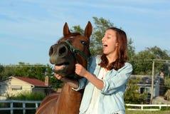 Une fille de l'adolescence rit avec son cheval Images libres de droits